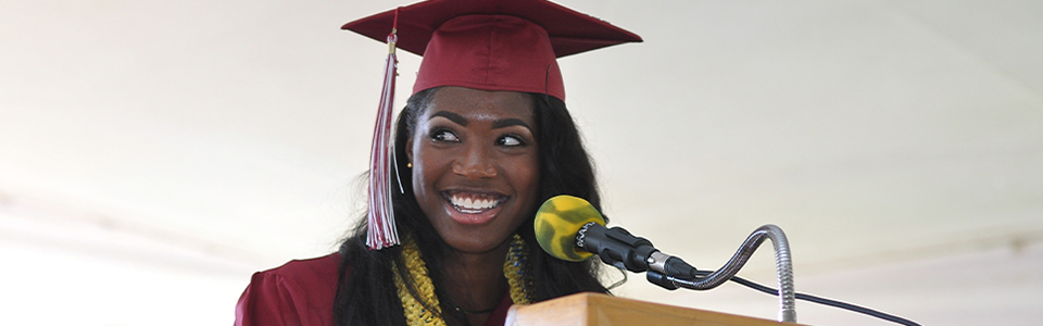 Student stands at podium on graduation day with a big smile