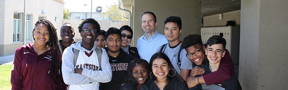 A group of students pose for a photo with Eastside principal Chris Bischof