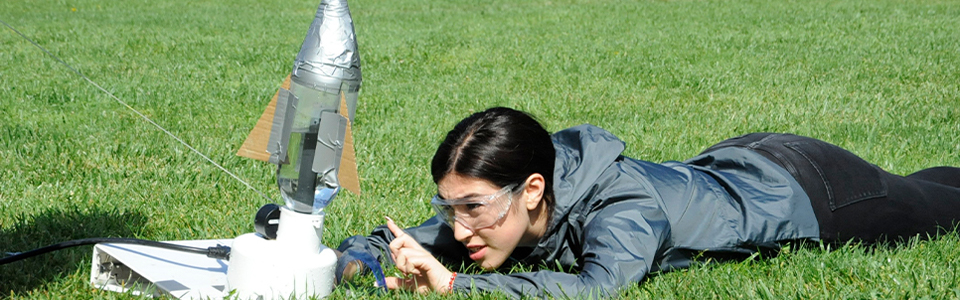 A student lies in the grass, setting up a bottle rocket